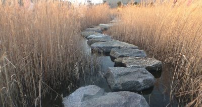Photo of a stone path along a winding waterway through a field.