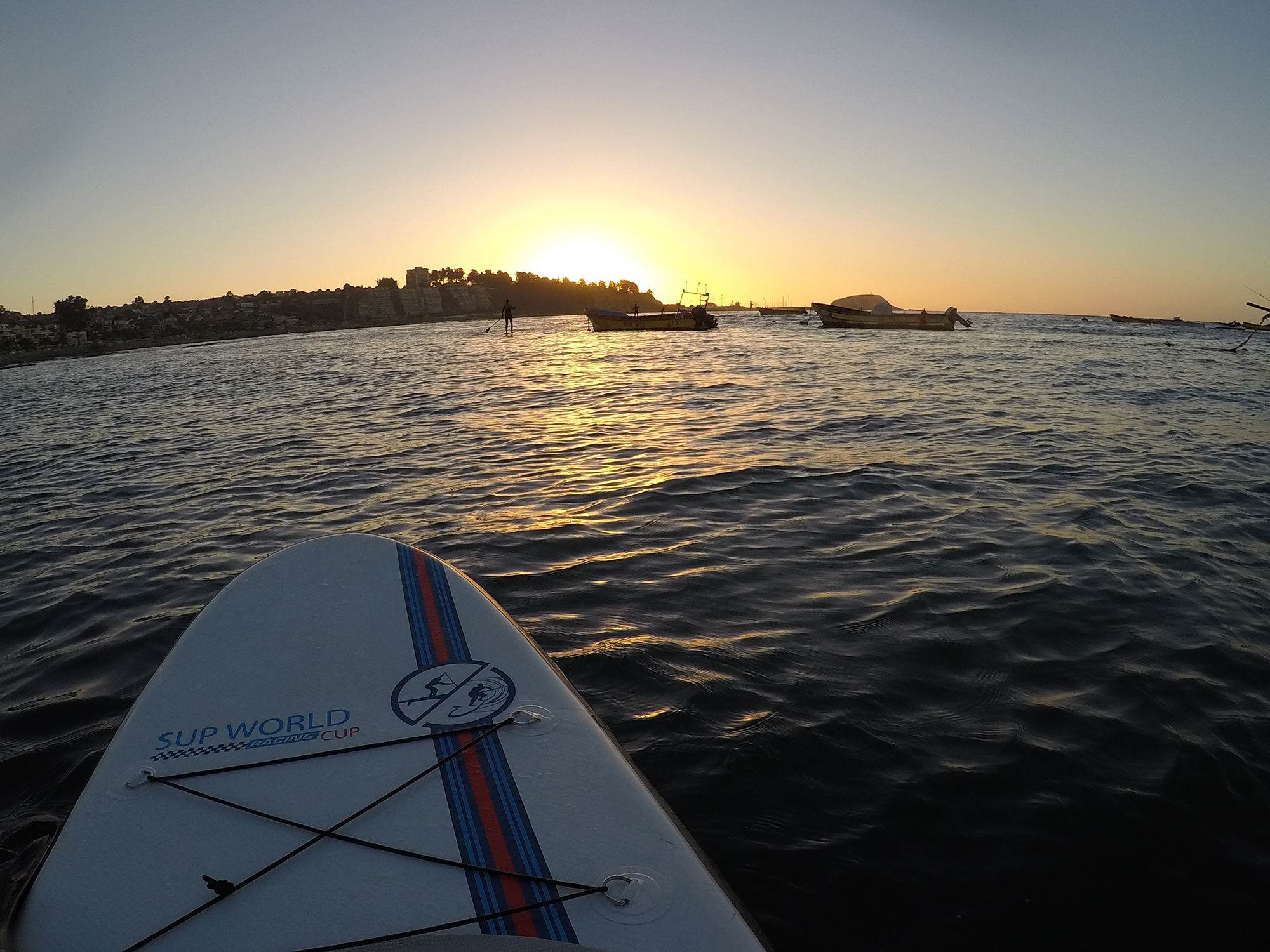 the tip of a paddle board on the water with the sun setting.