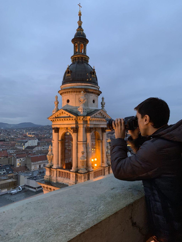 Nicolas looking through his camera in to a European landscape
