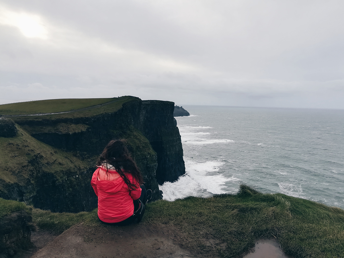 Hannah sitting on the Cliffs of Moher in Ireland