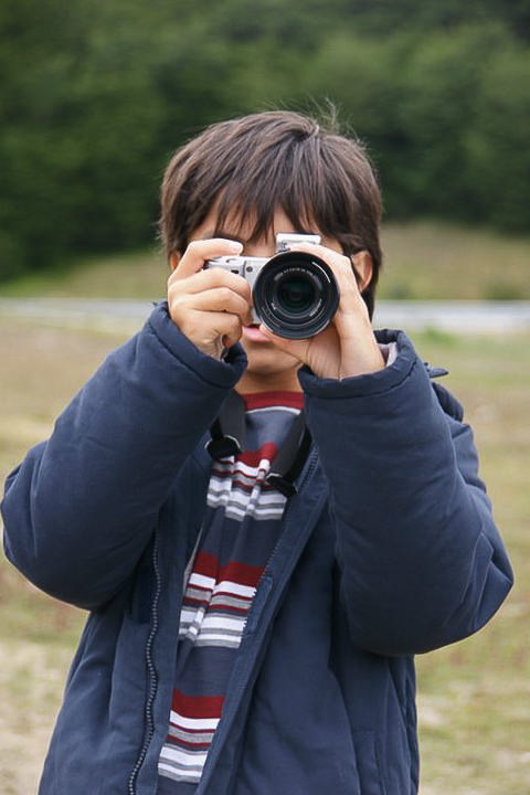 Nicolas as a small boy holding up a camera over his face