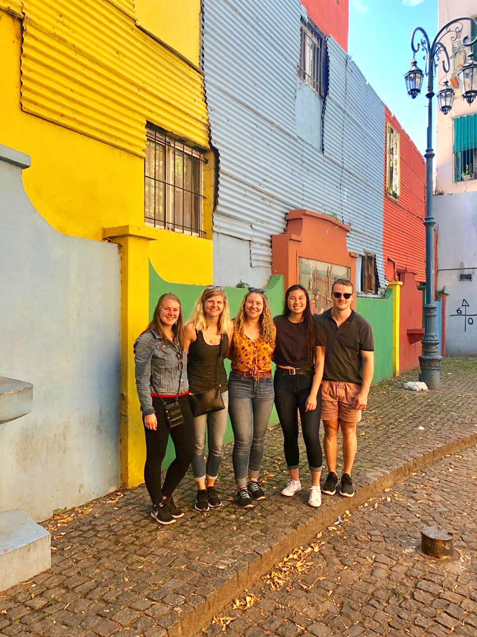 5 friends standing against a bright green and yellow wall