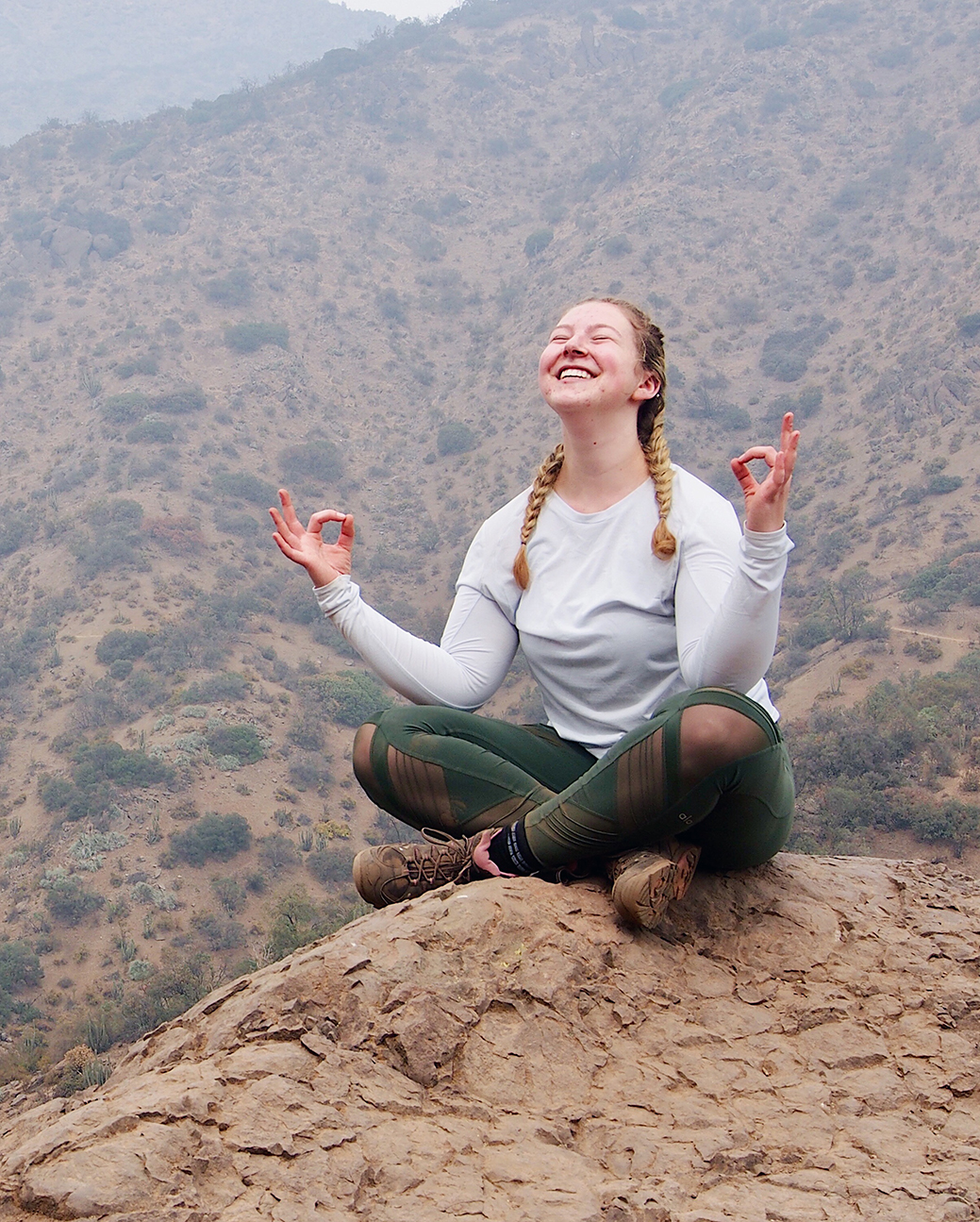 Alexa sitting in a meditative post on top of mountain in the Andes.