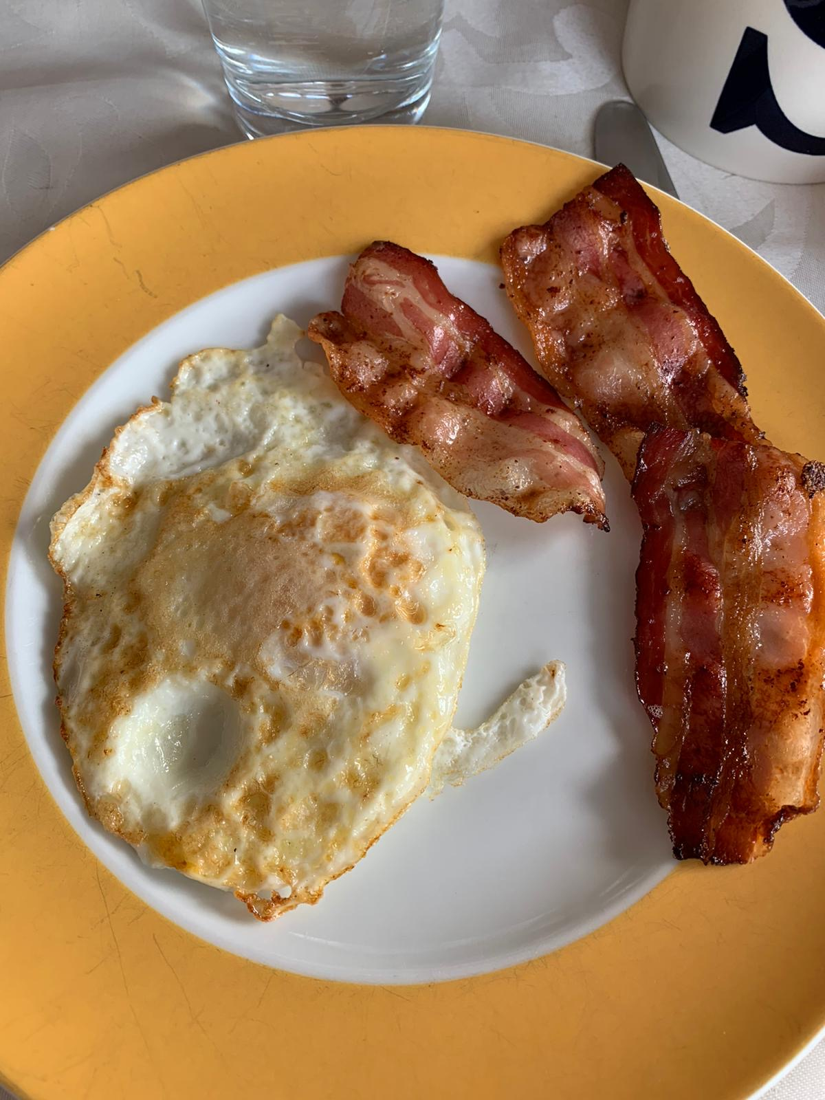 bacon and eggs over easy on a yellow plate