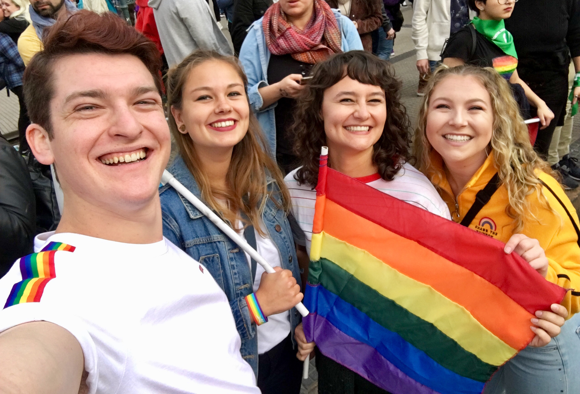 Alexa and her friends holding up a rainbow flag at the pride parade.