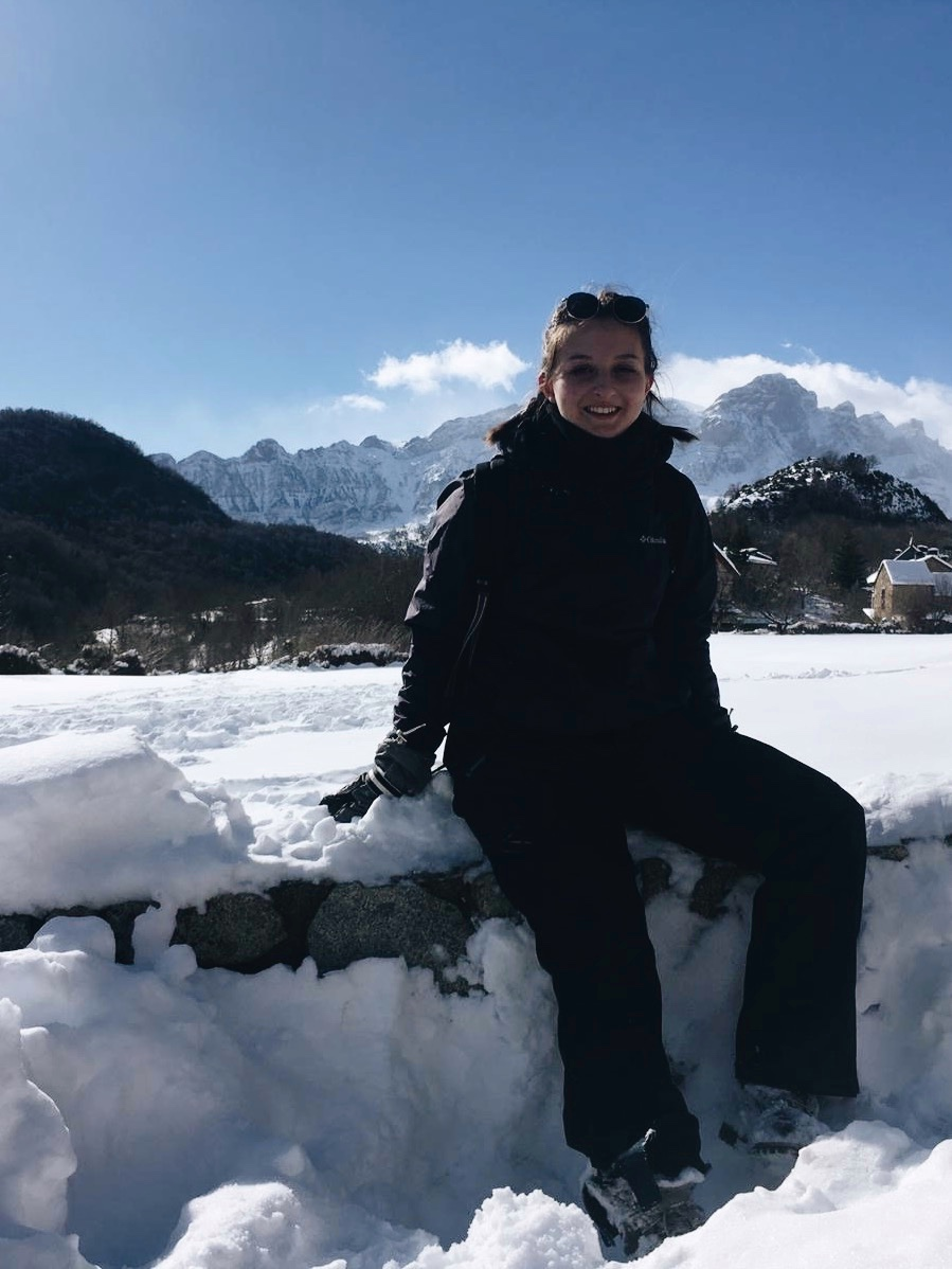 Alex sitting on a snowbank in a snowsuit with mountains in the background