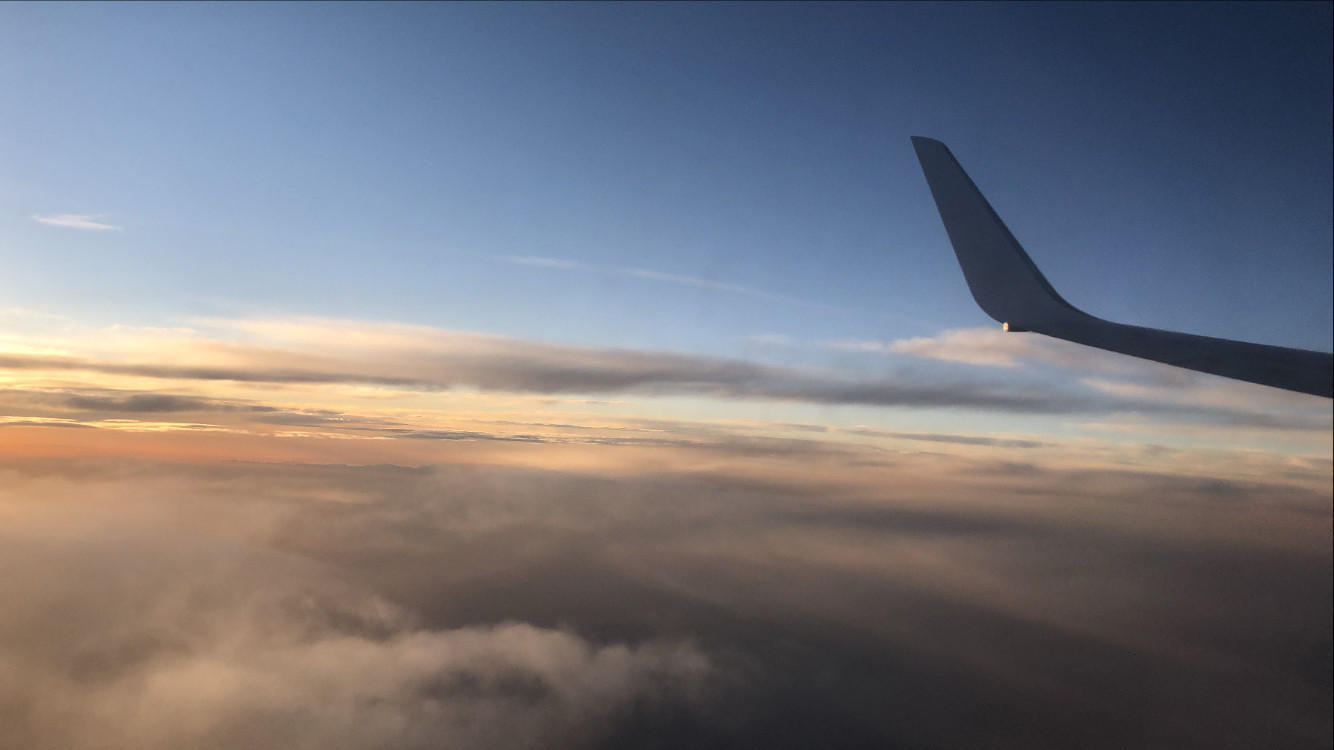 The end of the plane's wing over the clouds