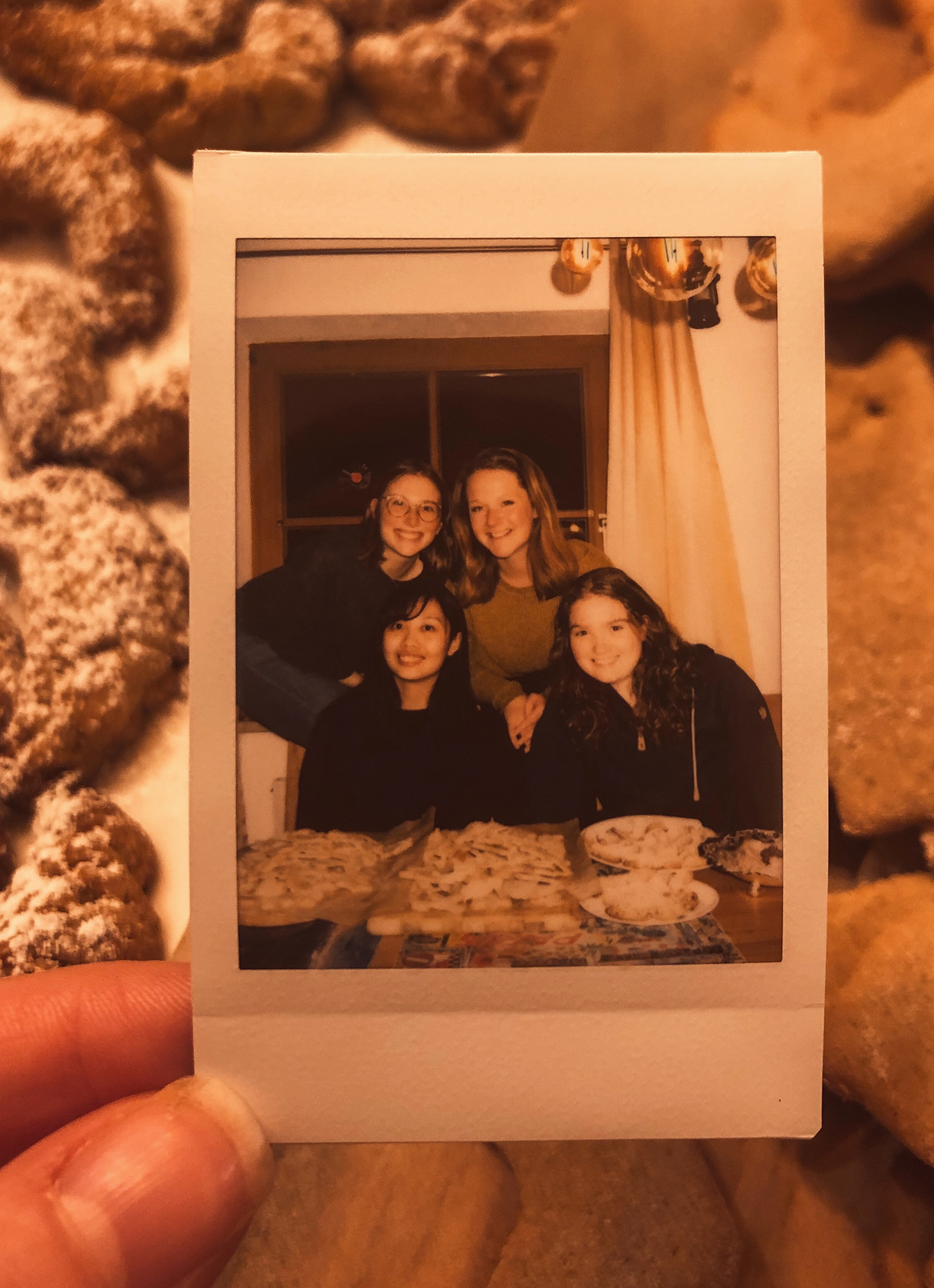 Ceiledh thumb holding a paloroid photo of her with 3 friends. Cookies in the background.