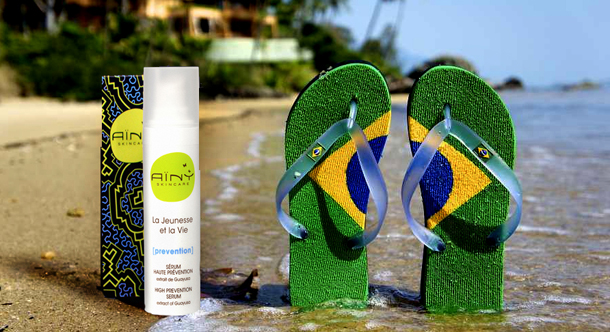 AINY products on the beach with sandals with the brazillian flag on them.