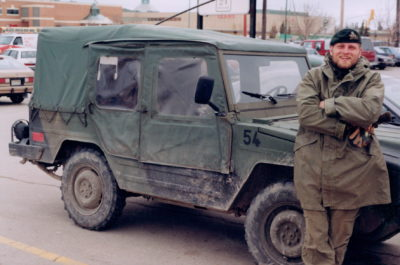 Captain Andrew Webb in uniform leaning on the hood of a military jeep.