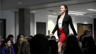 a female student wearing a blazer, white shirt and a red skirt walks down the walkway at the BCMC fashion show with the audience looking on