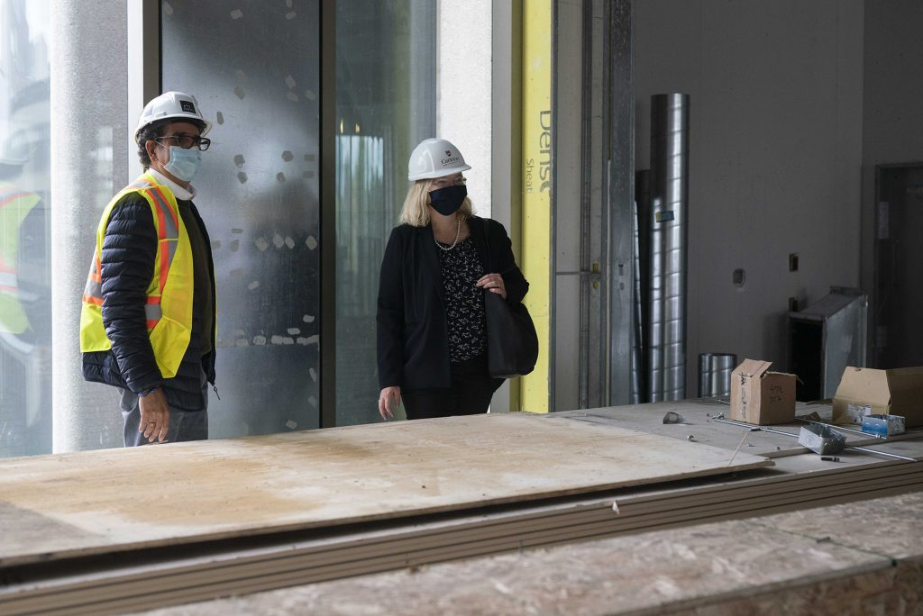 Siamak Hariri and Dana Brown wearing hared hats and masks inside the Nicol Building under construction