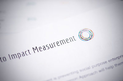 "Close up of paper with part of the title showing that reads, ""Impact Measurement"""
