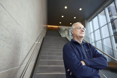 Professor Francois Brouard, Sprott School of Business in front of a staircase with his arms crossed