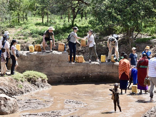 Carleton University students collecting water at a mud dam with local women and children in rural Tanzania.