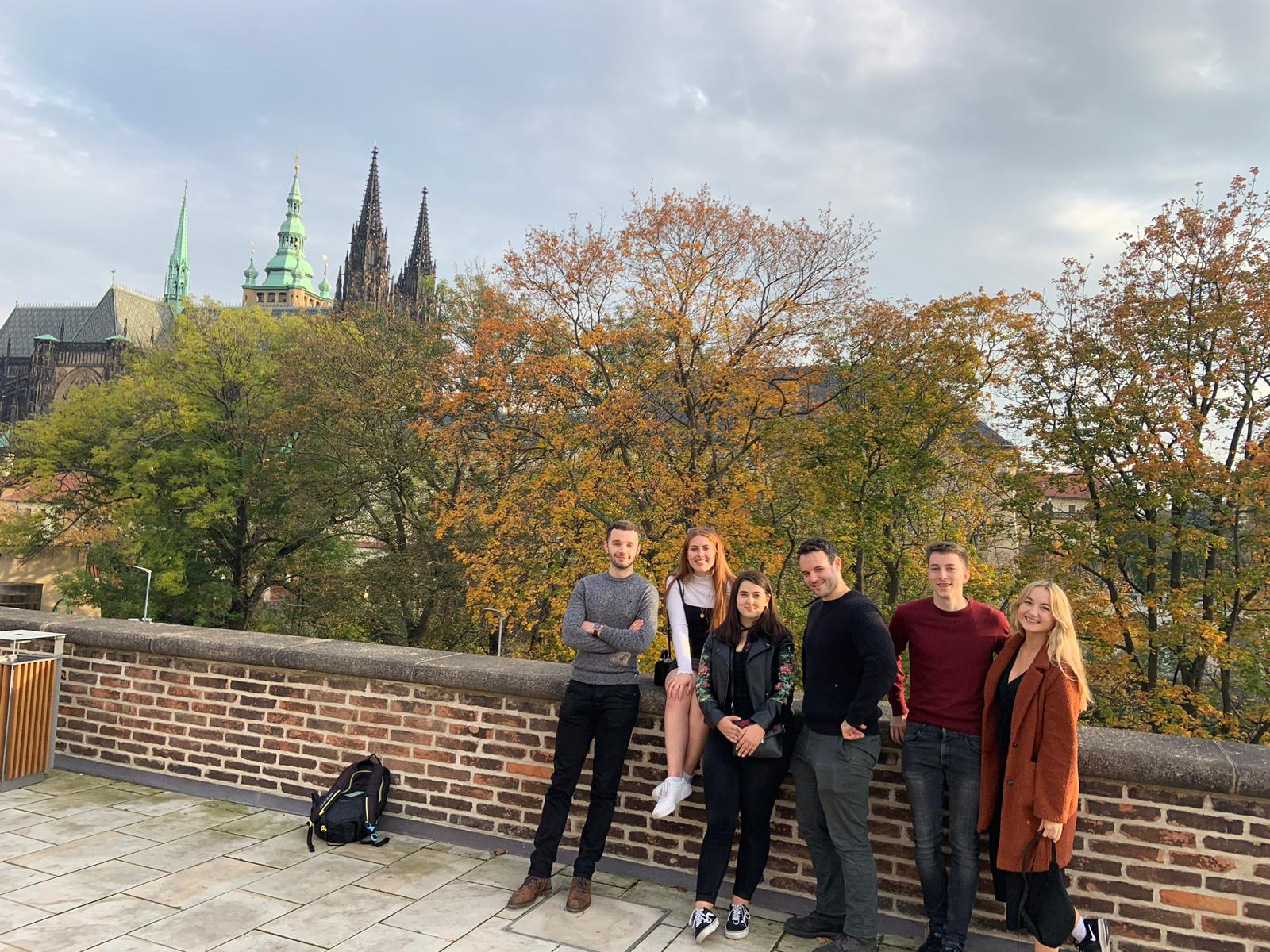 5 students in front of a stone wall with a castle in the background