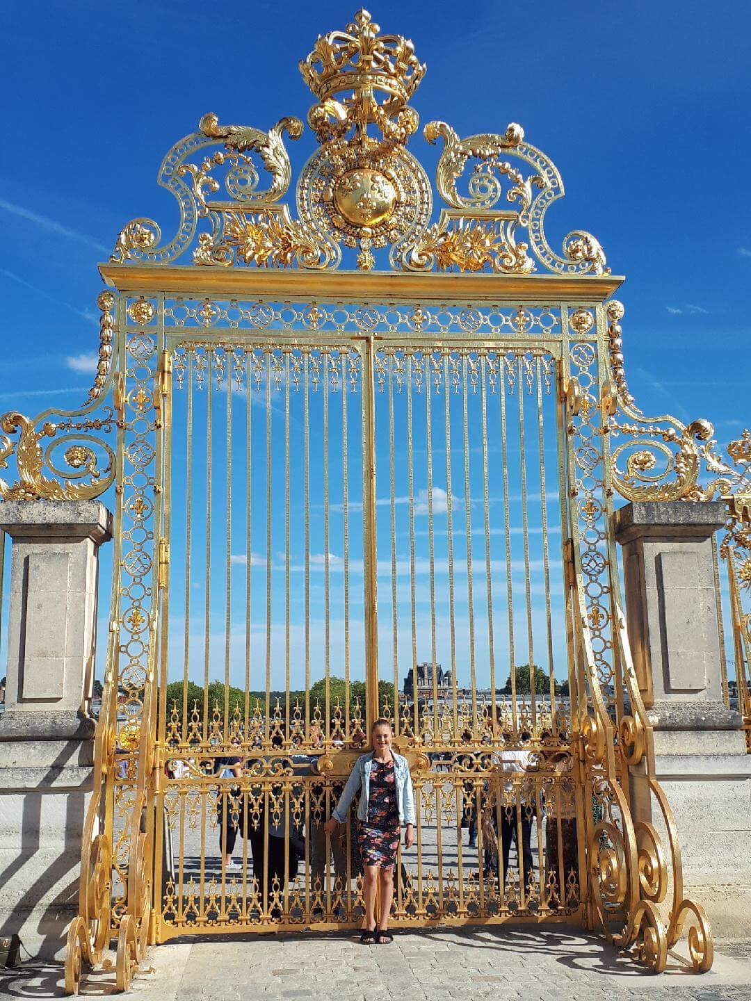 Sarah Jane standing in front of Palace of Versailles, 'Golden Gates'
