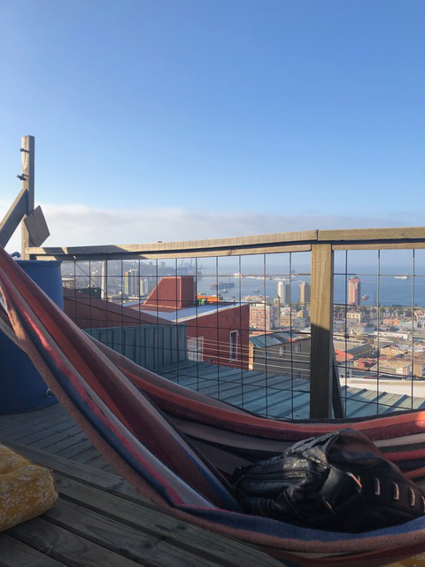 A hammock on a rooftop with the view of the mountains in the distance