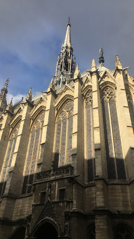 The exterior of Sainte-Chapelle, looking up at the tall church.