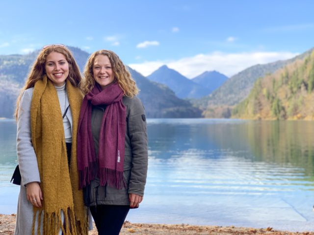 Ceiledh and Lauren in scarves in front of the water with mountains in the background.