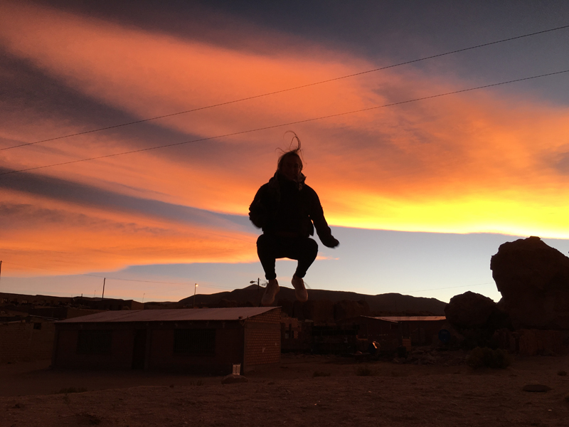 A shilhouette of Alexandra posing on a hill against an orange sunset.