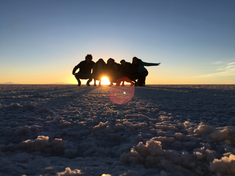 A silhouette of Alexandra and 4 friends posing in front of a sunset