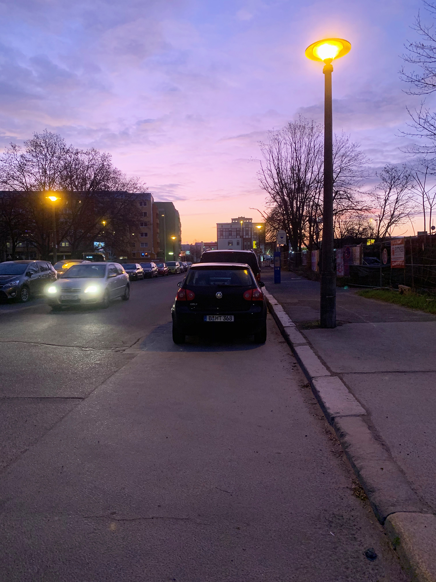 The sunrise peeking out over the buildings with cars parked on the road.