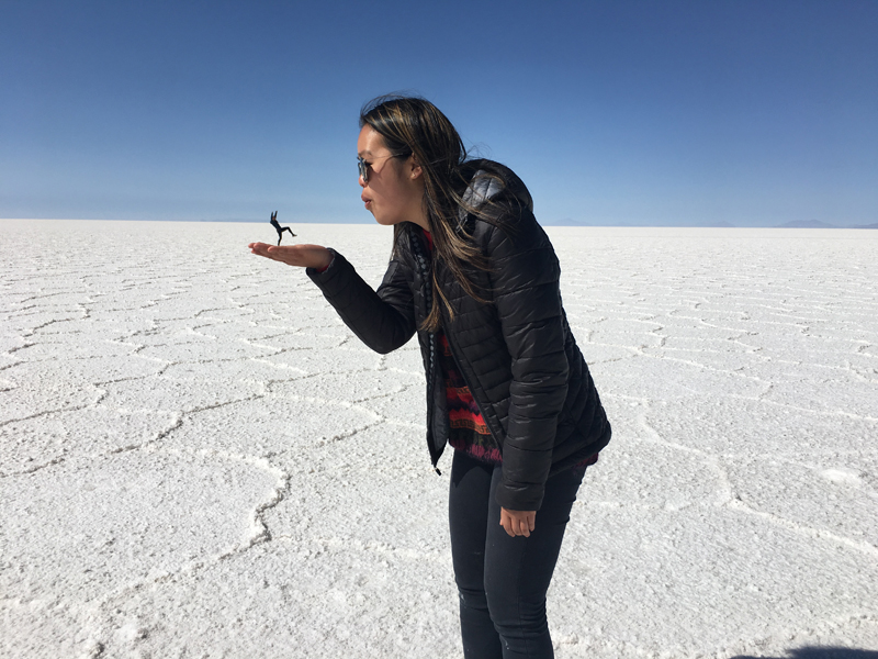 Alexandra playing with perspective and pretending to hold a friend in her hand, standing in the salt lands.