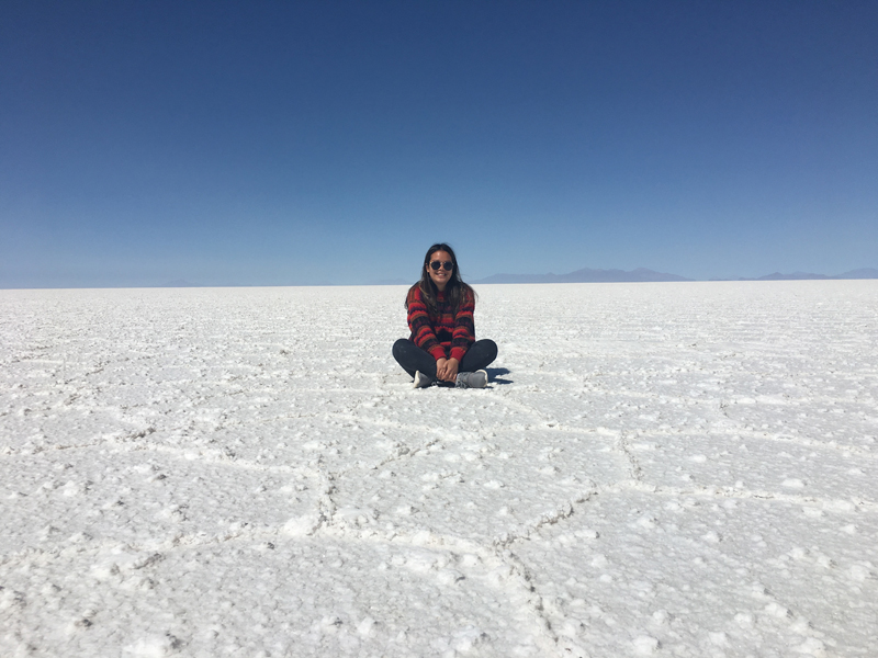 Alexndra sitting in the middle of the salt lands with a clear blue sky