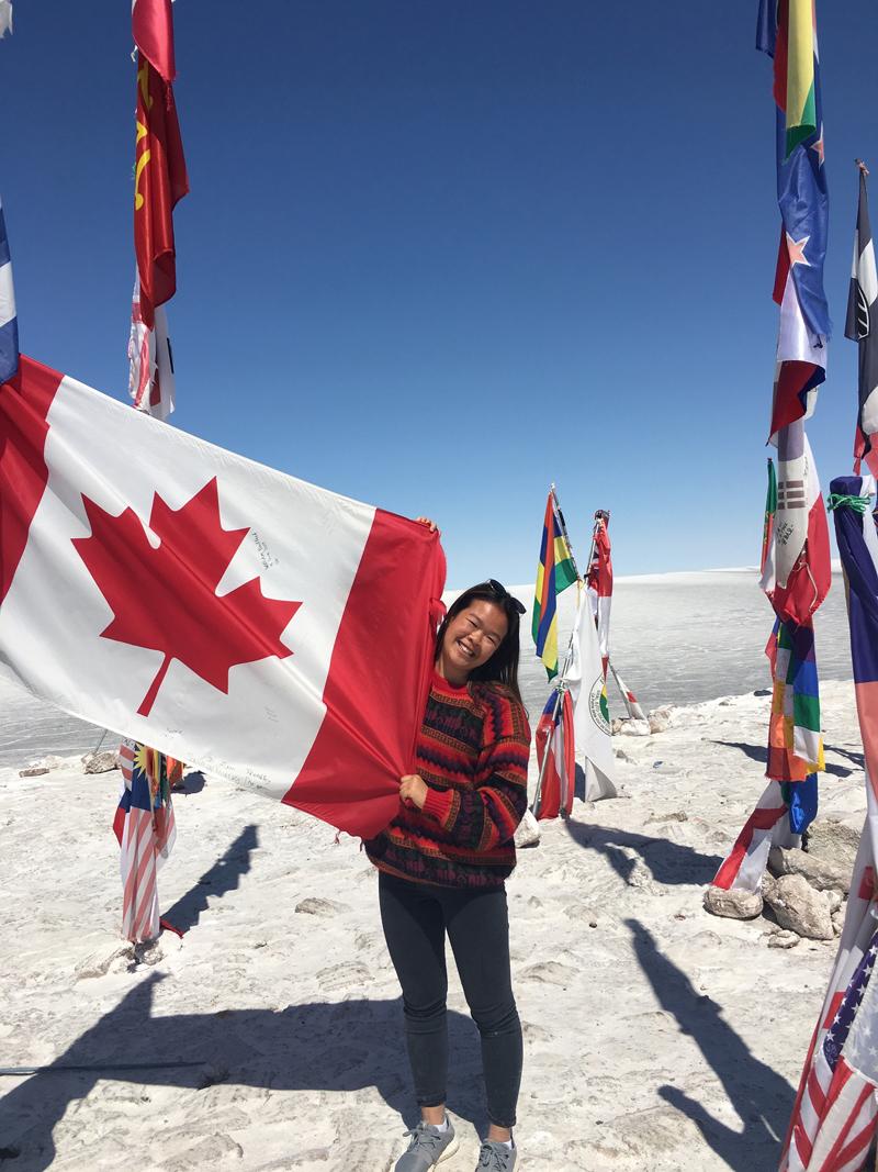 Alexandra holding up a big Canadian flag.