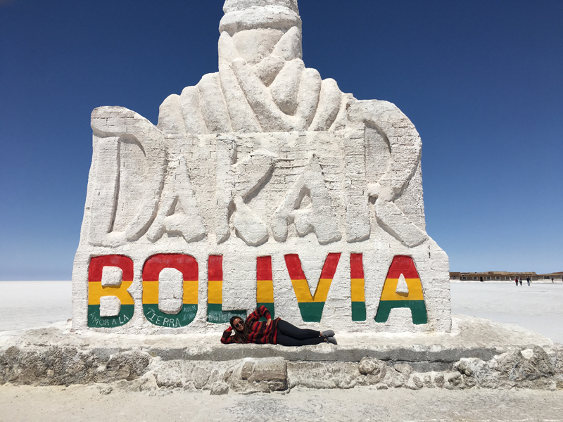 Alexandra lying down in front of a giant sign for Dakar, Bolivia.