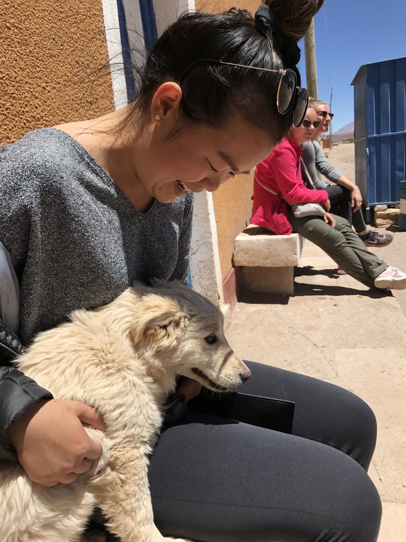 Alexandra holding a small yellow dog