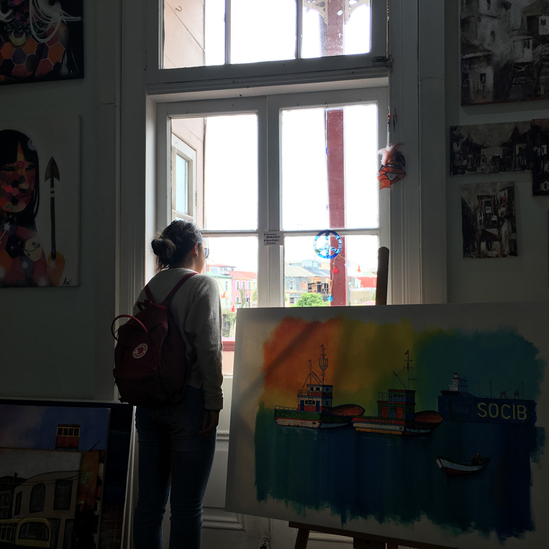 Alexandra looking out a window in an art gallery