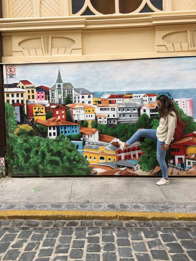 Alexandra pretending to step on a house in a painting on the street