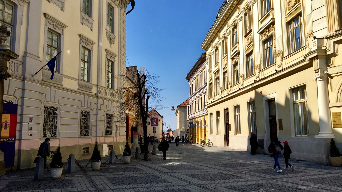 The main square of Sibiu with the sun shining on the ornate buildings.