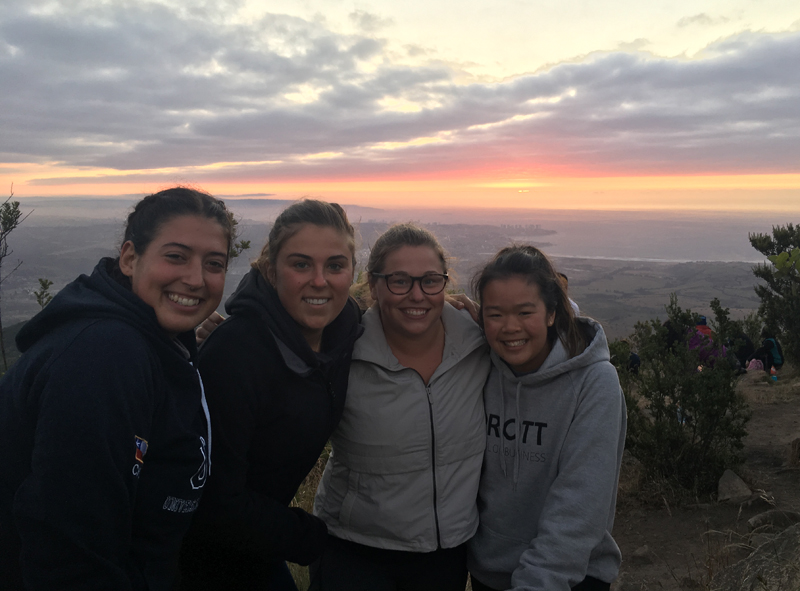 alexandra and 3 friends in front of a sunset