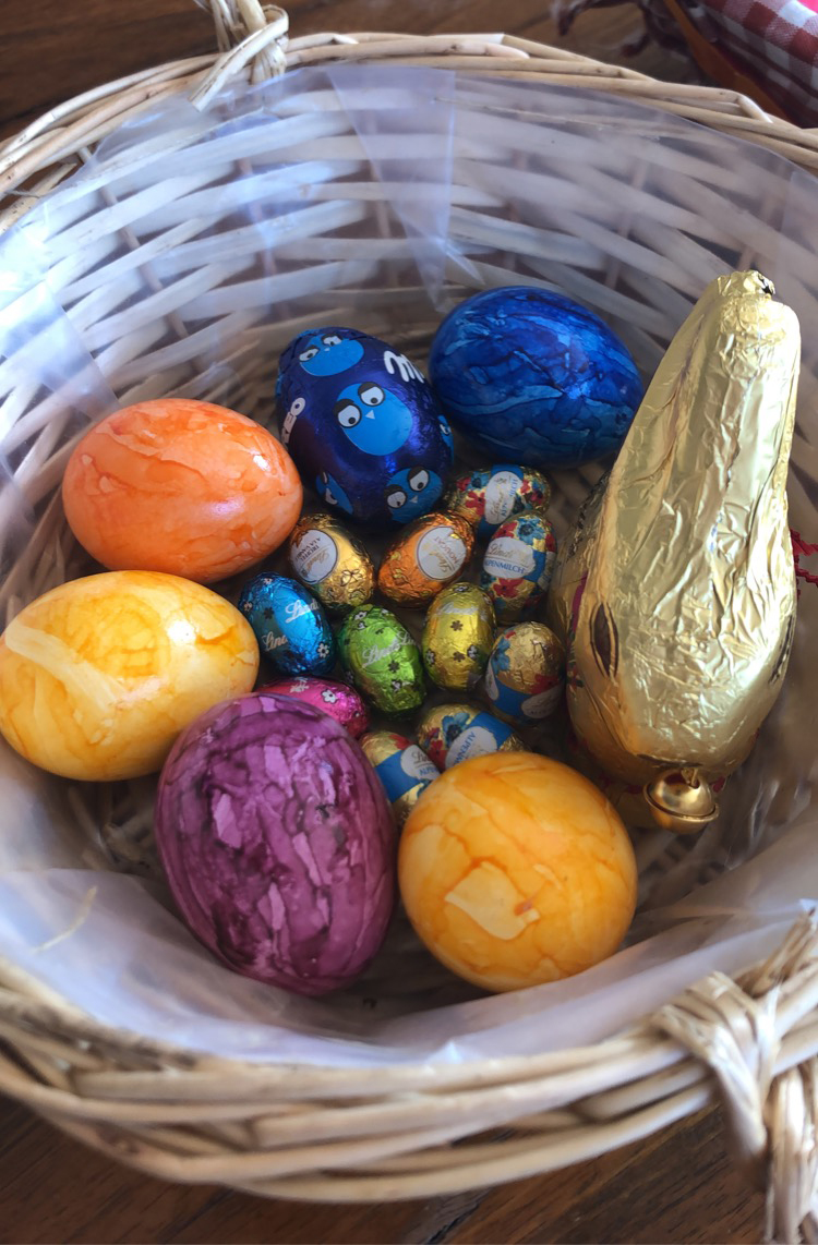 chocolate eggs, a chocolate bunny and colourful died hard boiled eggs in an easter basket