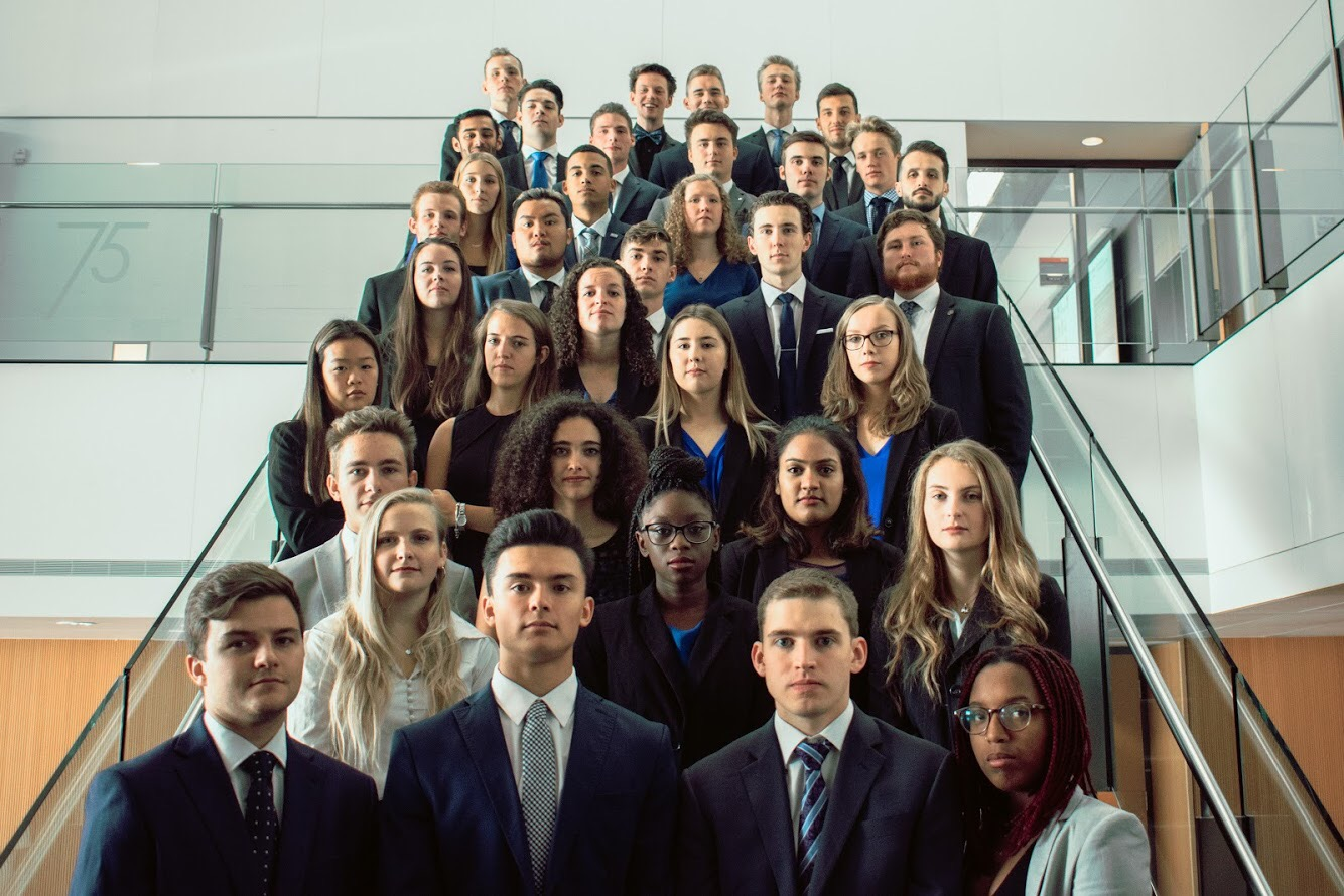 JDCC Sprott team delegates in business attire, arranged on a staircase
