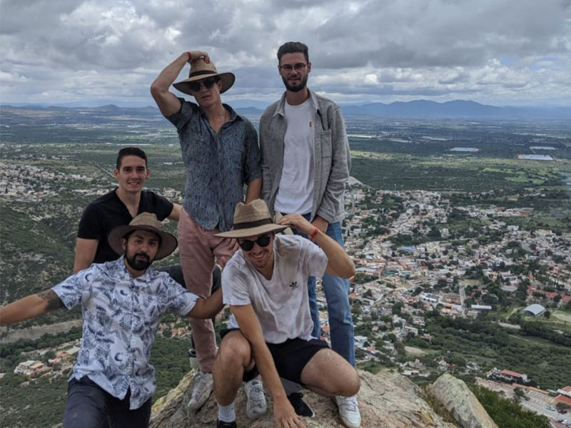 A picture of Jacob Sams and four of his friends on top of a high hill in San Miguel de Allende, Mexico. You can see a view of the city behind them.