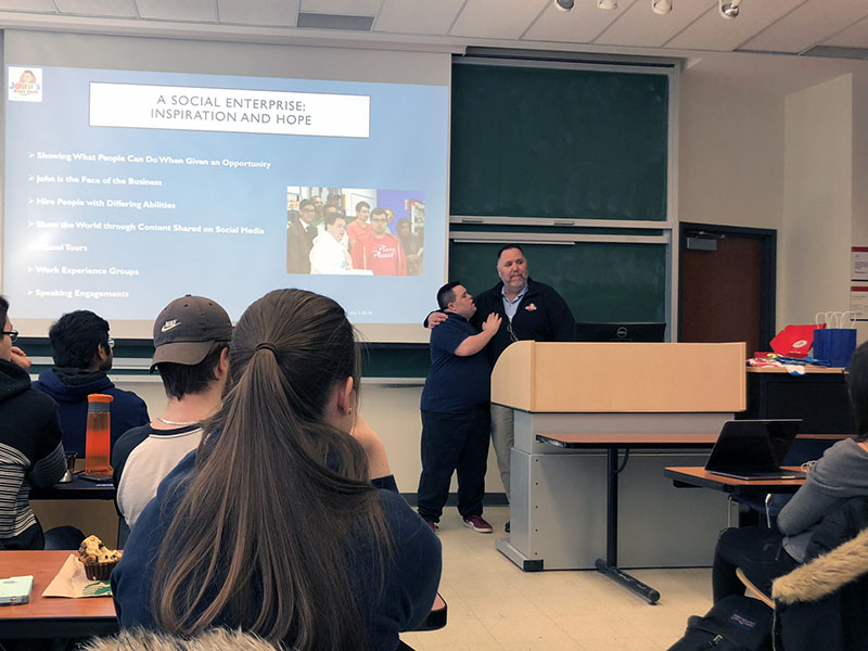 John and Mark Cronin embrace while they share the story of John's Crazy Socks social enterprise to Carleton entrepreneurship students.