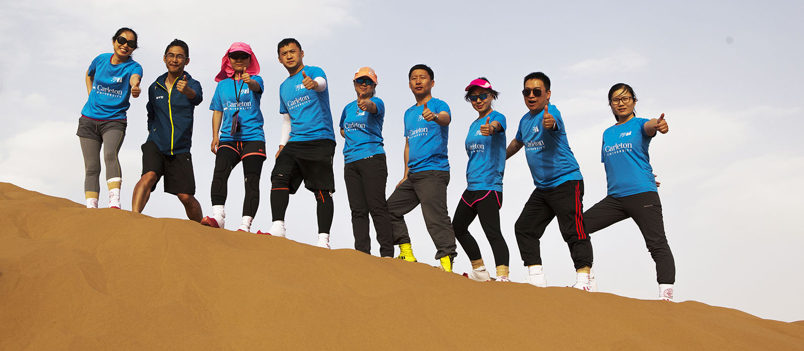 The Sprott MBA Shanghai student team lined up on a sand dune at the 2018 Asia-Pacific Desert Challenge in the Gobi Desert.