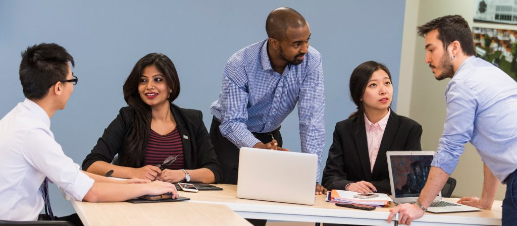 A diverse group of MBA students sitting around a large table carrying multiple conversations.