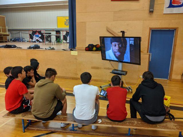 Carletonn student speaking to Masset youth in a gymnasium via Zoom.