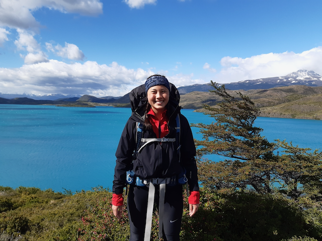 meagan bundled up for hiking in patagonia with the water and clouds in the background