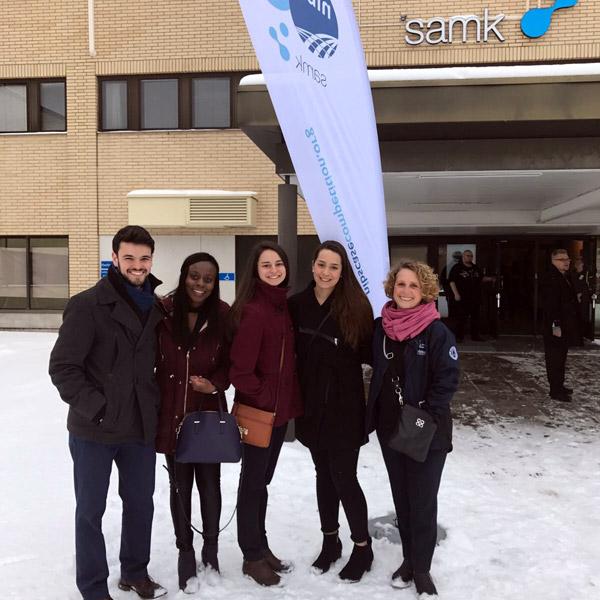Students and coach standing outside Satakunta University in Rauma, Finland.