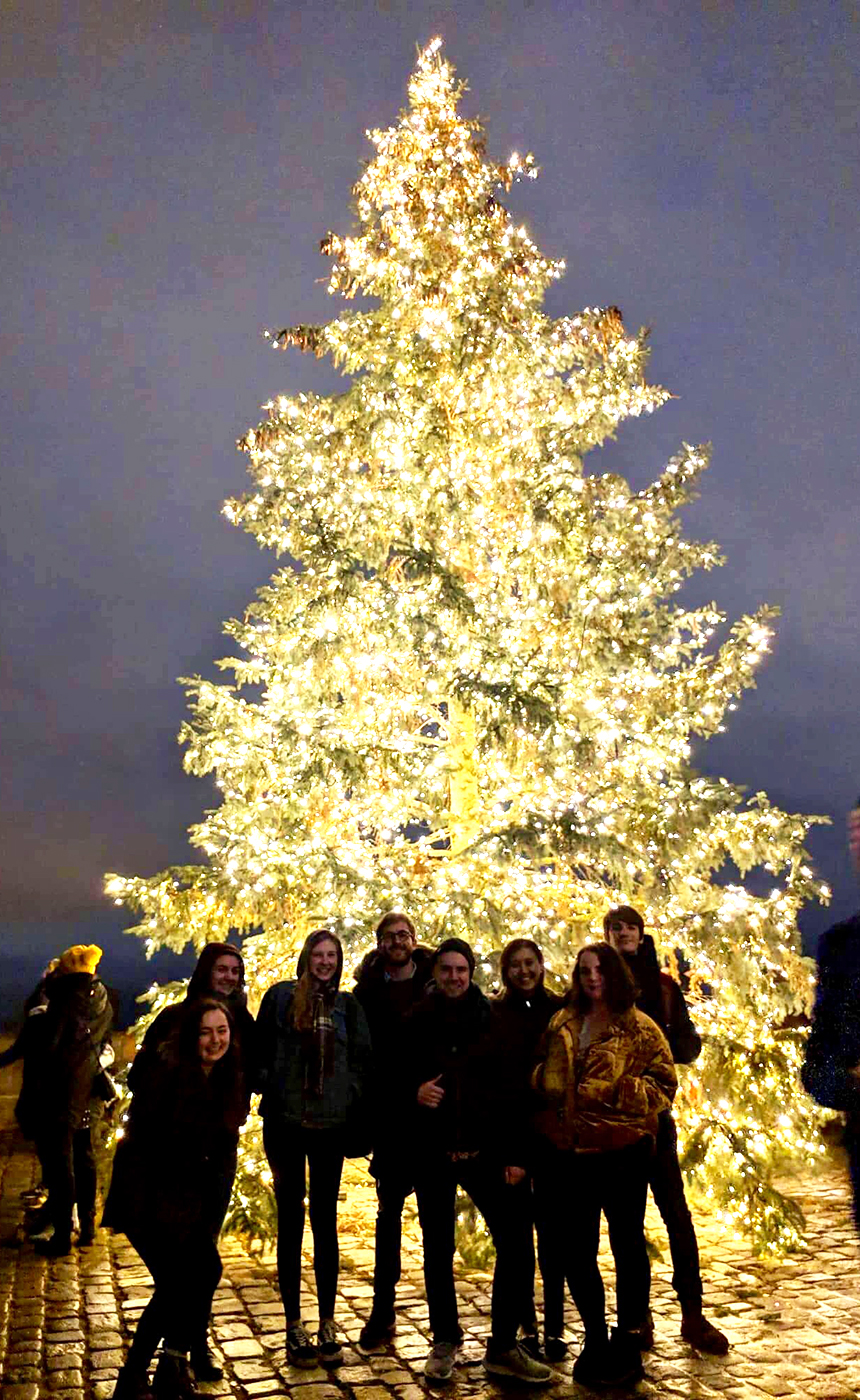 Jasmine and friends in front of a lit up Christmas tree at dusk.