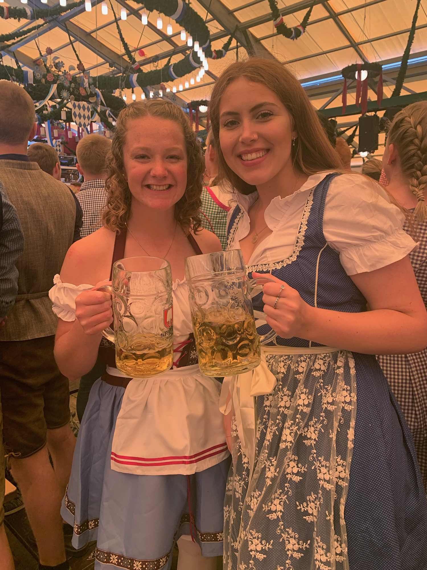 Ceiledh and Lauren wearing Dirndls and holding large beer steins