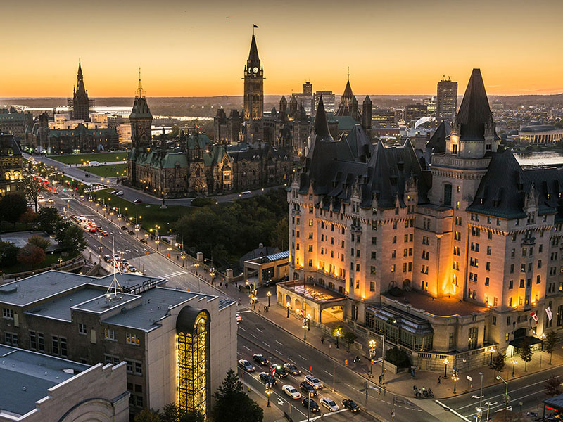 View overlooking Canada's Parliament Buildings and downtown Ottawa at dusk.