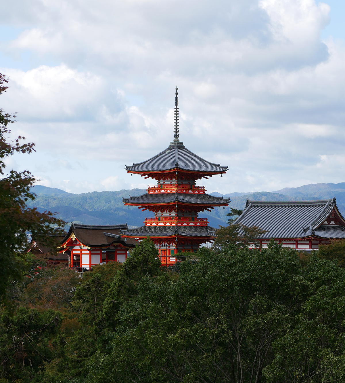 an orange temple in the distance, behind tree with the moutains in the distance