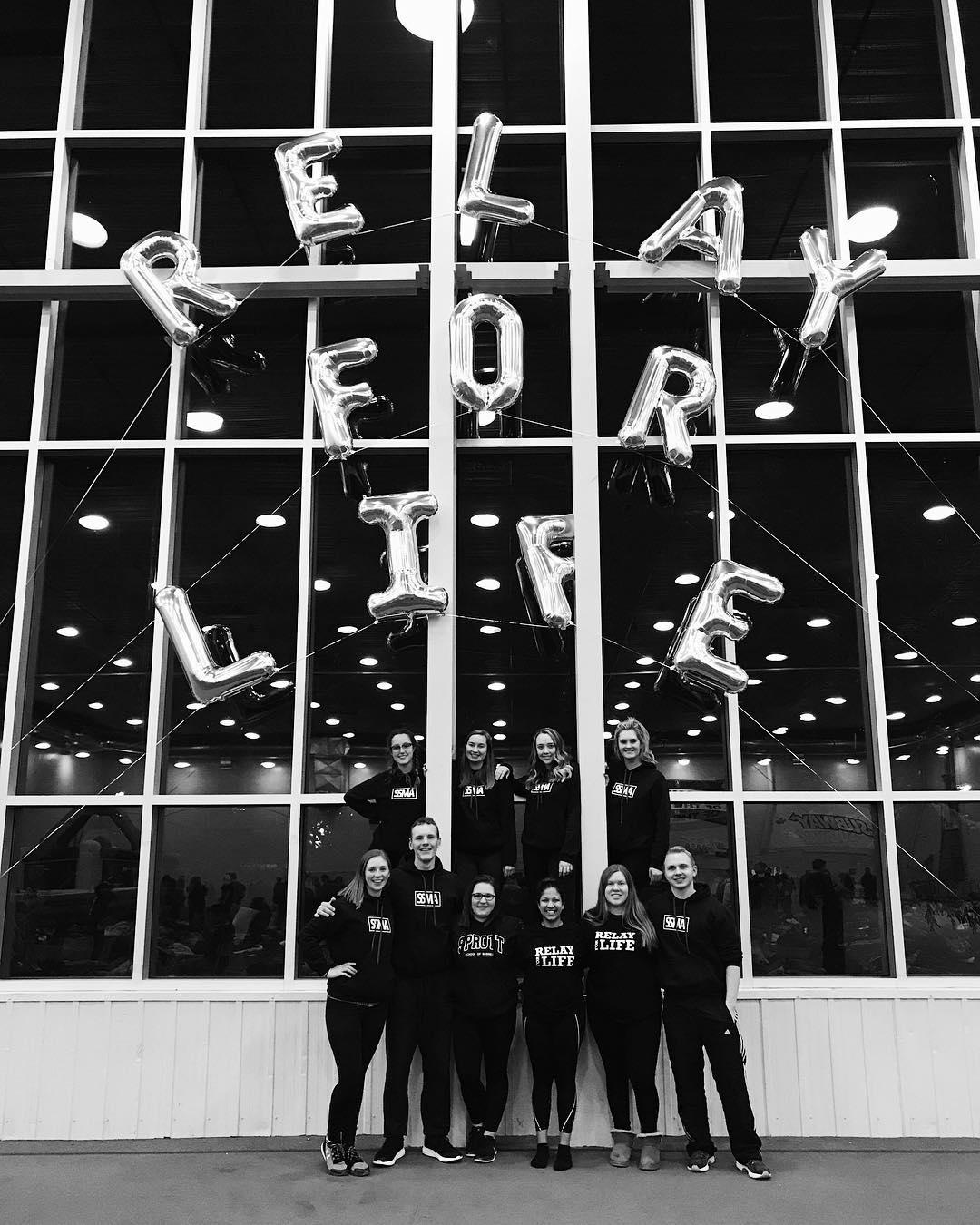 Sophia and her team members infront a large wall of window with balloons letters that spell out Relay for Life.